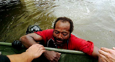 A Hurricane Katrina survivor is pulled from the flood water