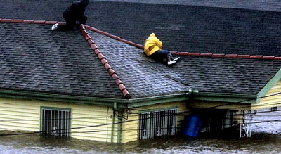 Two Hurricane Katrina survivors find refuge on their roof as they await rescue