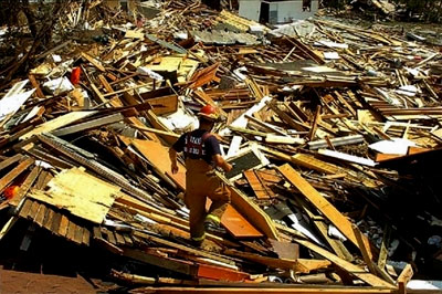 A firefighter walks atop destroyed houses
